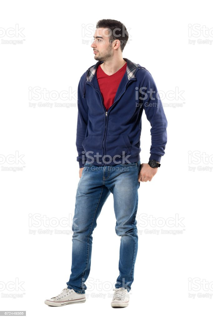 Cool smiling young handsome man in sweatshirt with hands in back pockets looking away stock photo