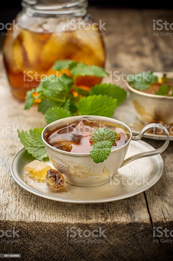 Cool summer tea with mint and ice cubes in a stock photo