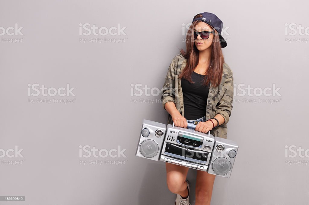 Cool teenage girl in hip hop outfit holding a radio stock photo