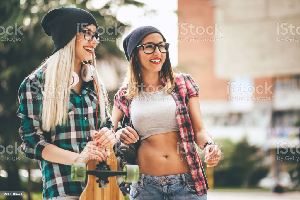 Cool teenage longboarders smiling and talking stock photo