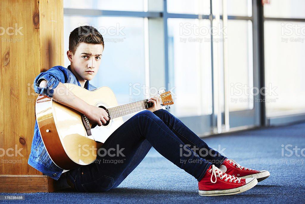 Cool teenager with guitar sitting on carpet in hallway royalty-free stock photo