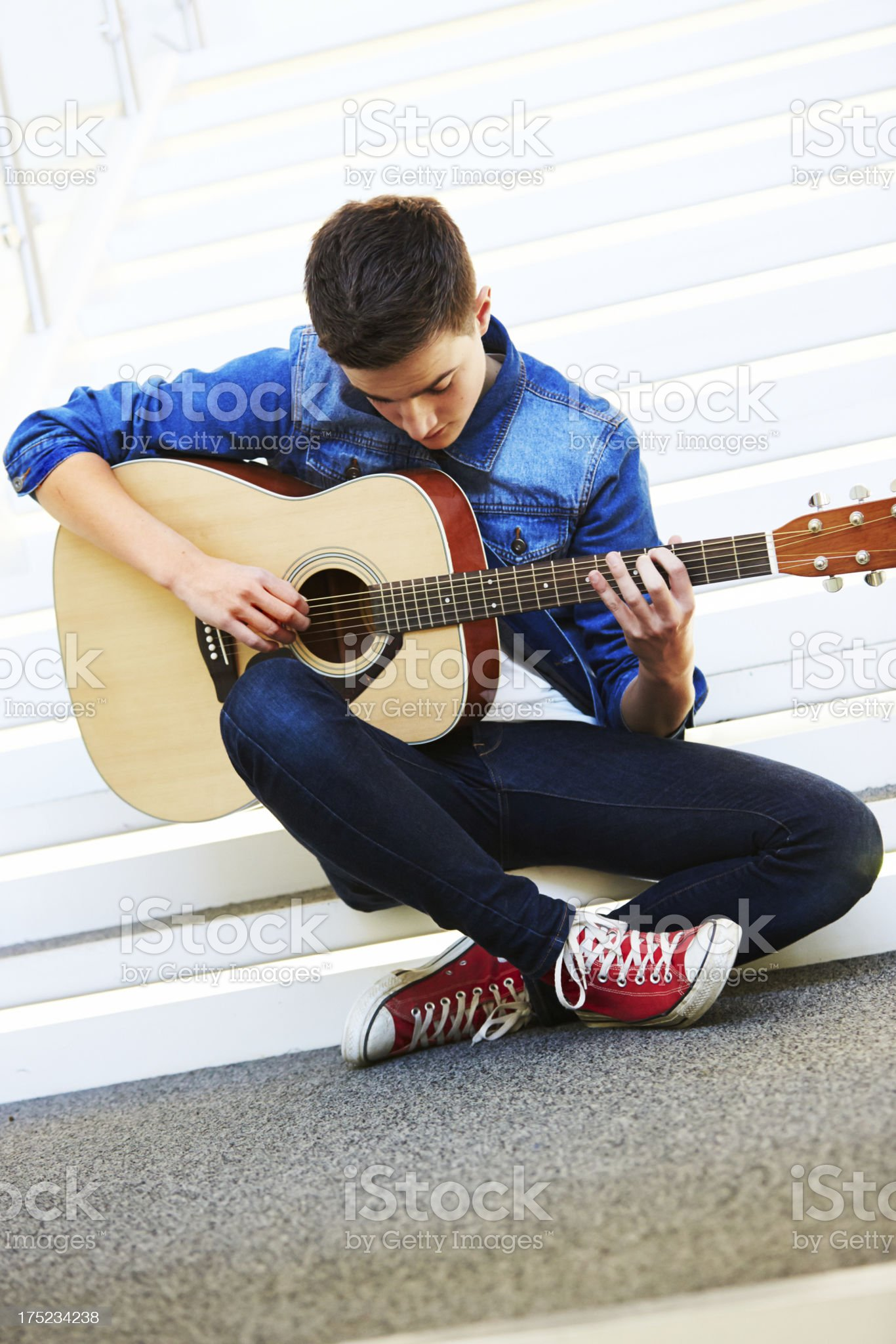 Cool teenager with guitar sitting on stairs royalty-free stock photo