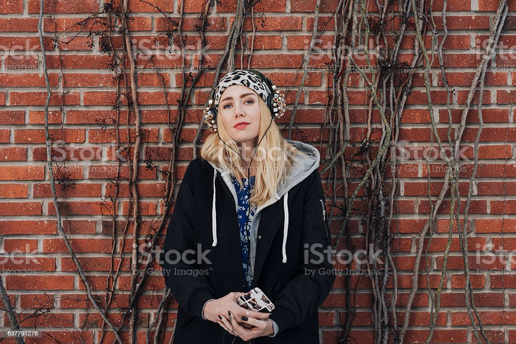 Cool urban fashionable woman listening to music stock photo