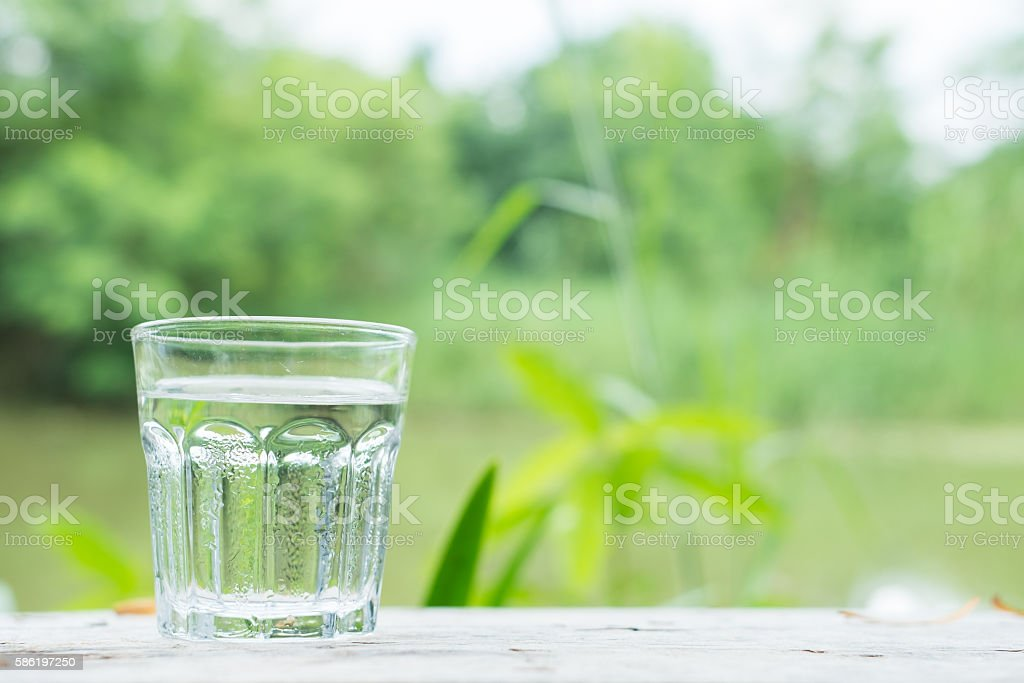 Cool water on wooden desk with Lake background stock photo
