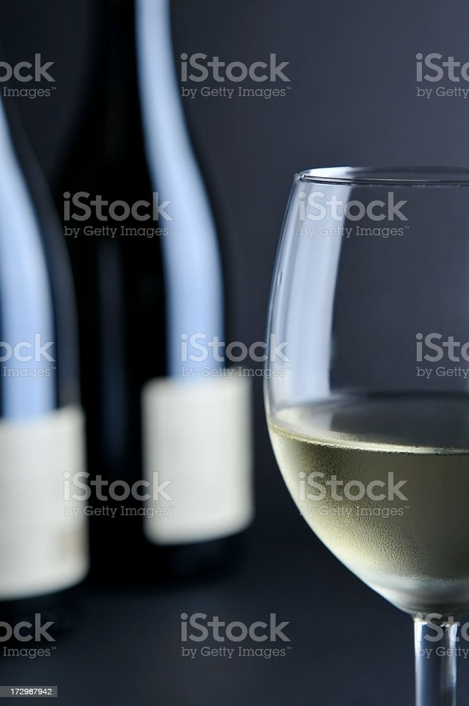 Cool white wine glass in foreground, two bottles in the background royalty-free stock photo