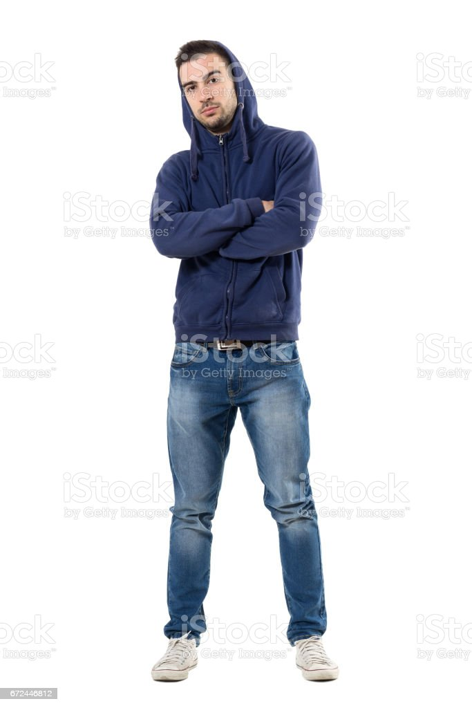 Cool young confident man in blue sweatshirt with crossed arms looking at camera stock photo