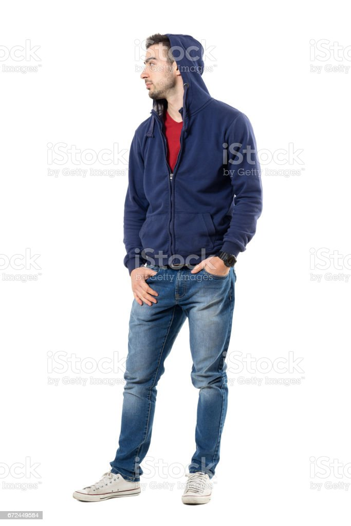 Cool young guy in hoodie with hands in pockets looking away stock photo