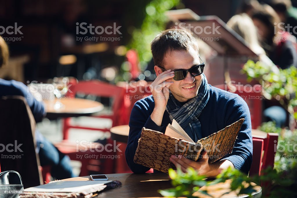 Cool young man in sunglasses ordering something at a street stock photo