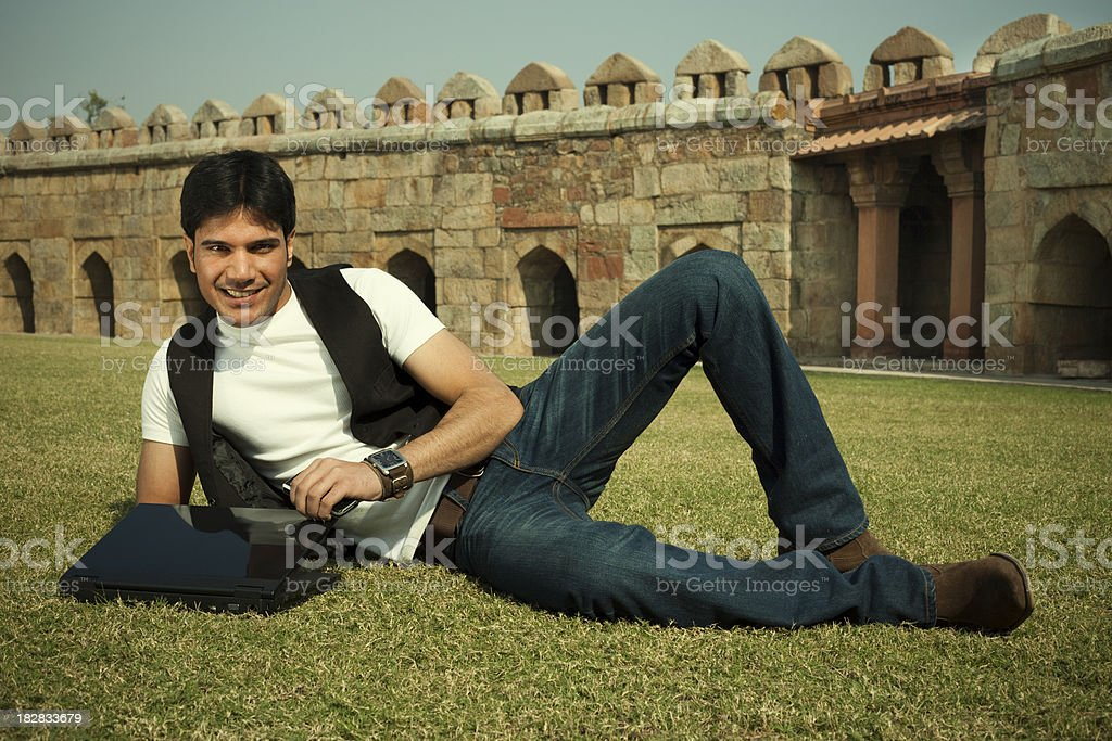Cool young man lying on grassy ground while using laptop royalty-free stock photo