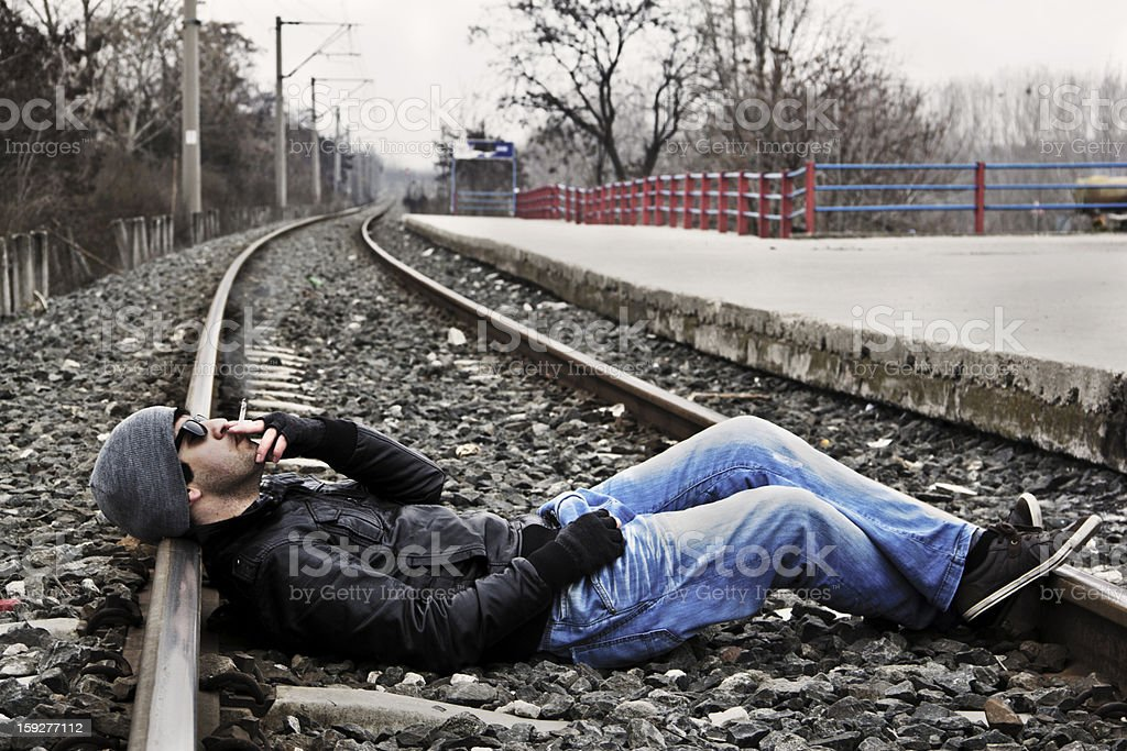 Cool young man smokin on railroad stock photo