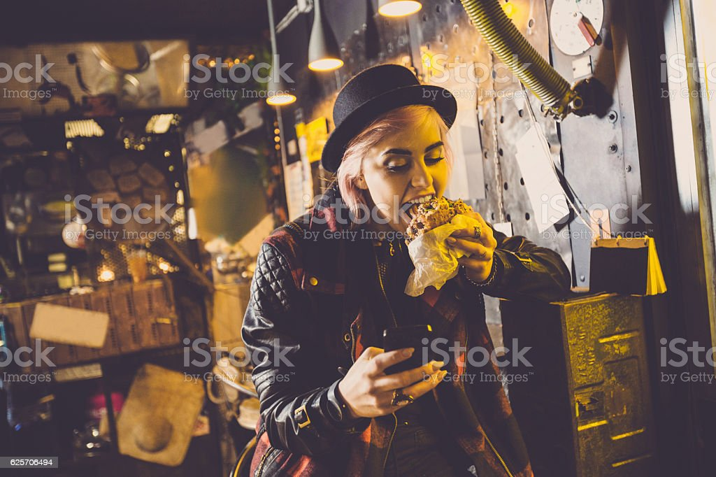 Cool young woman eating burger in pub, using smart phone stock photo