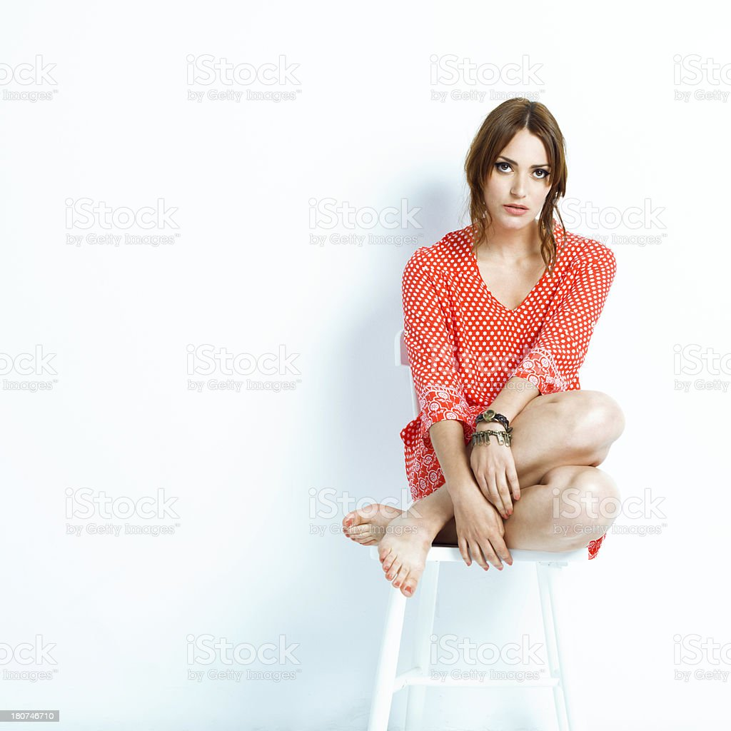 Cool young woman sitting on a white chair royalty-free stock photo