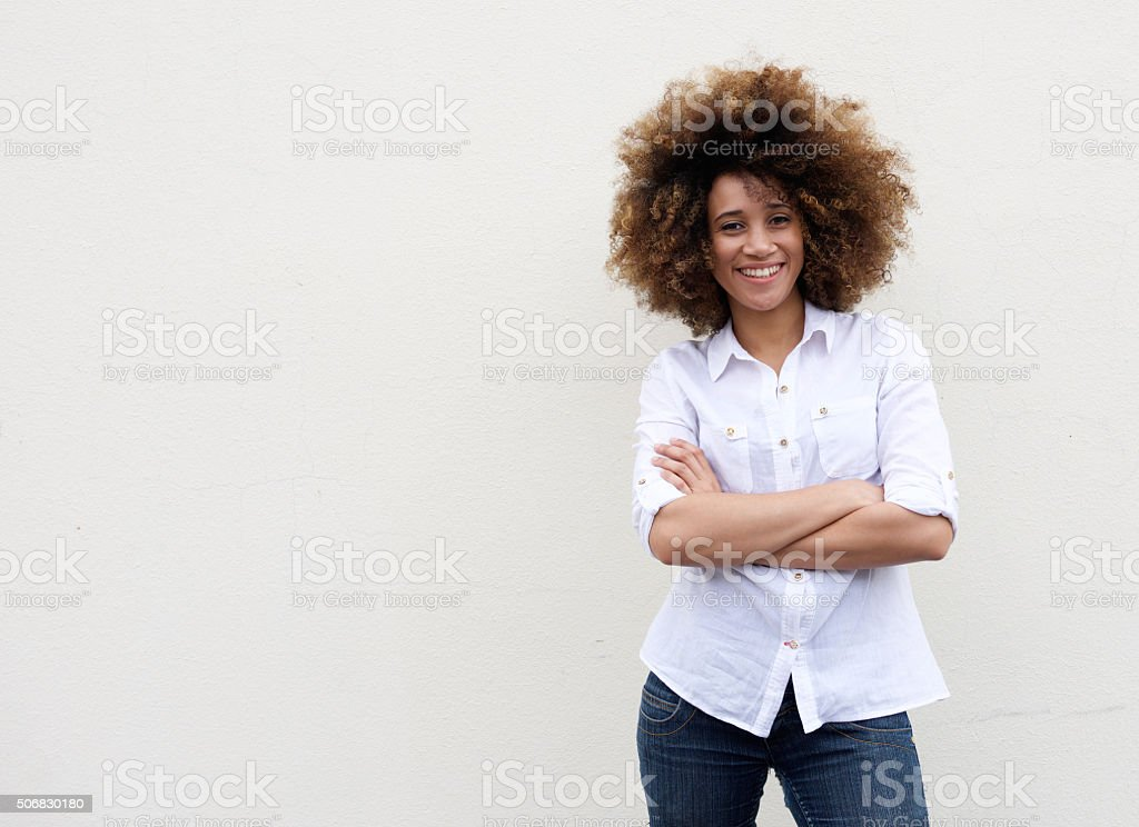 Cool young woman smiling with arms crossed stock photo