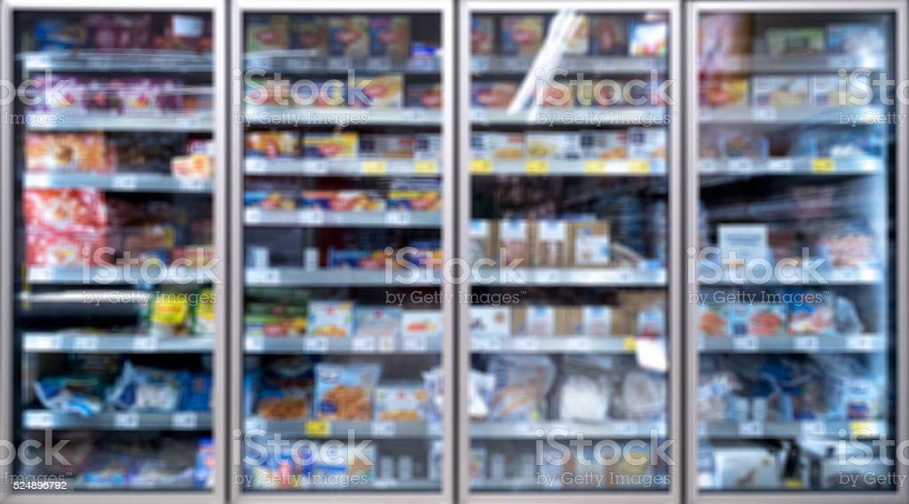 cooling shelves freezer in supermarket - blurred stock photo