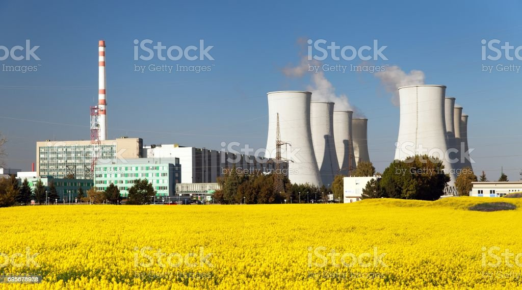 cooling tower with golden flowering field of rapeseed stock photo