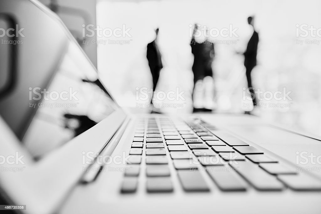 Cooperation behind laptop stock photo