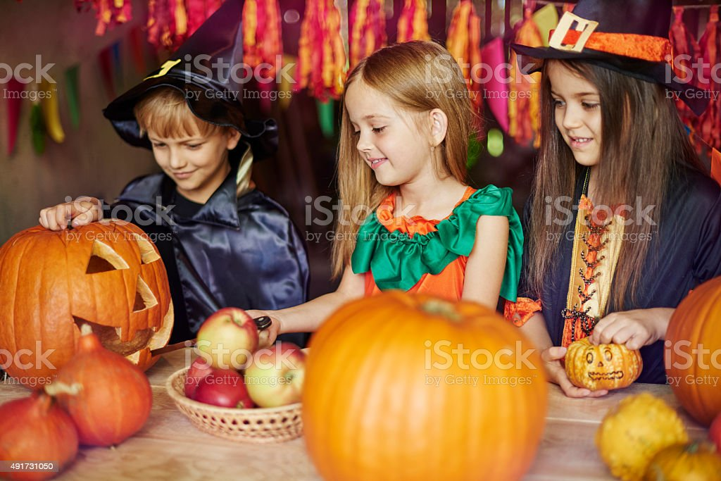 Cooperation during the work on carving a pumpkin stock photo