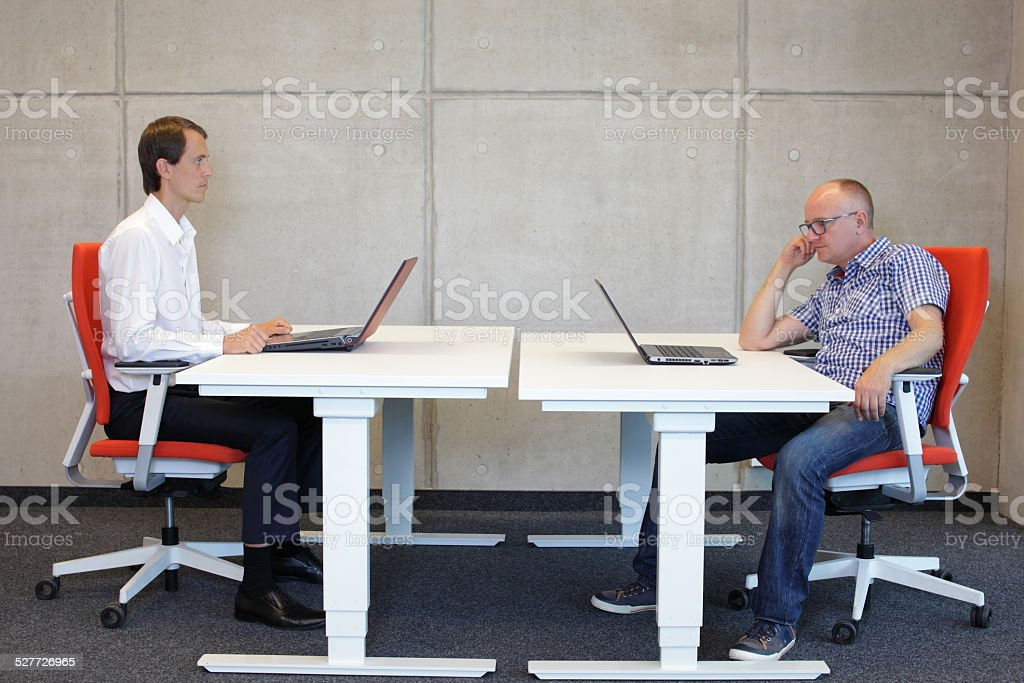 coorect and bad sitting postures at desk in office stock photo