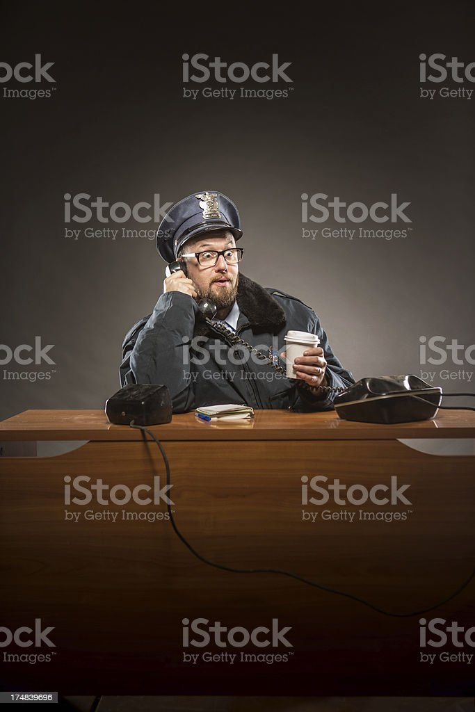 Cop on the Phone while Drinking Coffee royalty-free stock photo