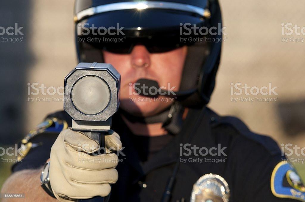 Cop pointing a radar gun at the camera stock photo
