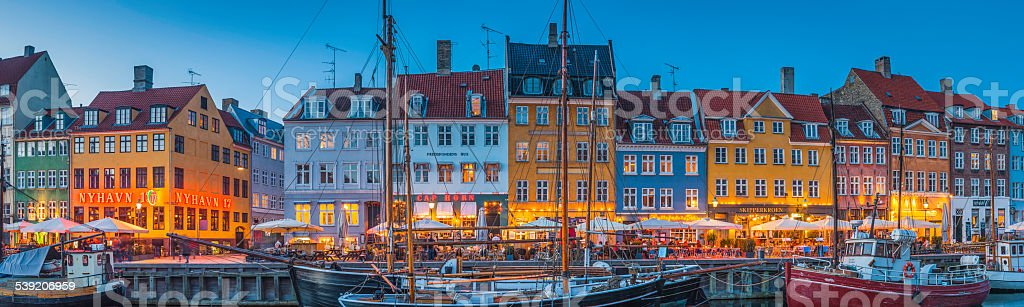 Copenhagen Nyhavn colorful bars and restaurants illuminated at dusk Denmark stock photo