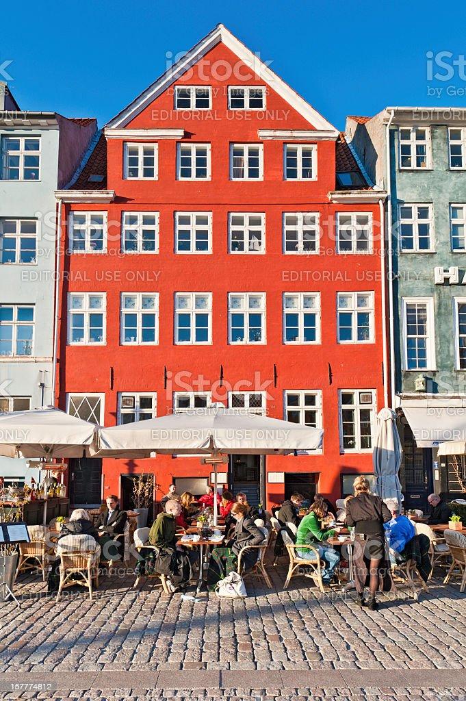 Copenhagen people sitting at pavement café outdoor restaurant Nyhavn Denmark stock photo