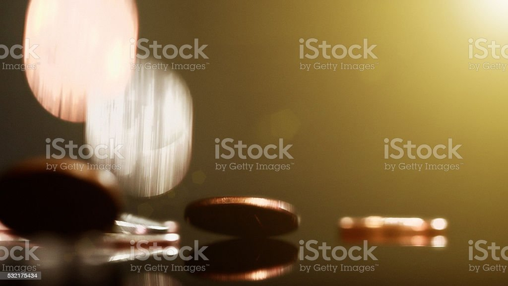 Copper and silver coins falling onto shiny surface stock photo