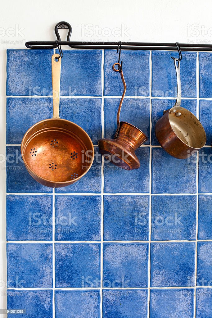 Copper kitchenware set. Pot, coffee maker, colander hanging on stock photo
