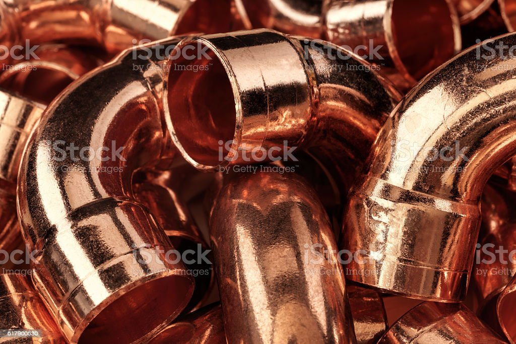 Copper pipes in a pile. Abstract background. stock photo