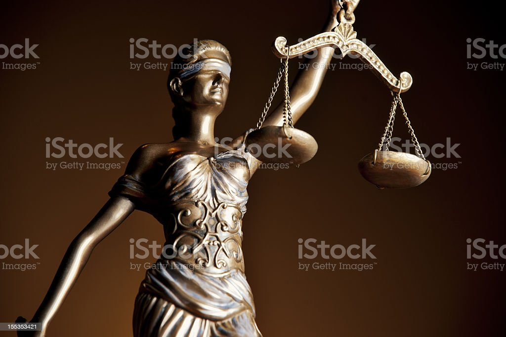 Copper statue of Themis holding scales against dark backdrop stock photo