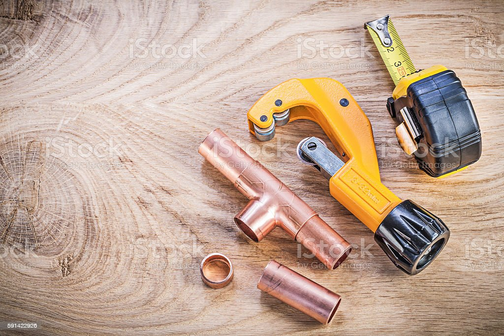 Copper water pipe cutter fittings tape measure on wood board stock photo