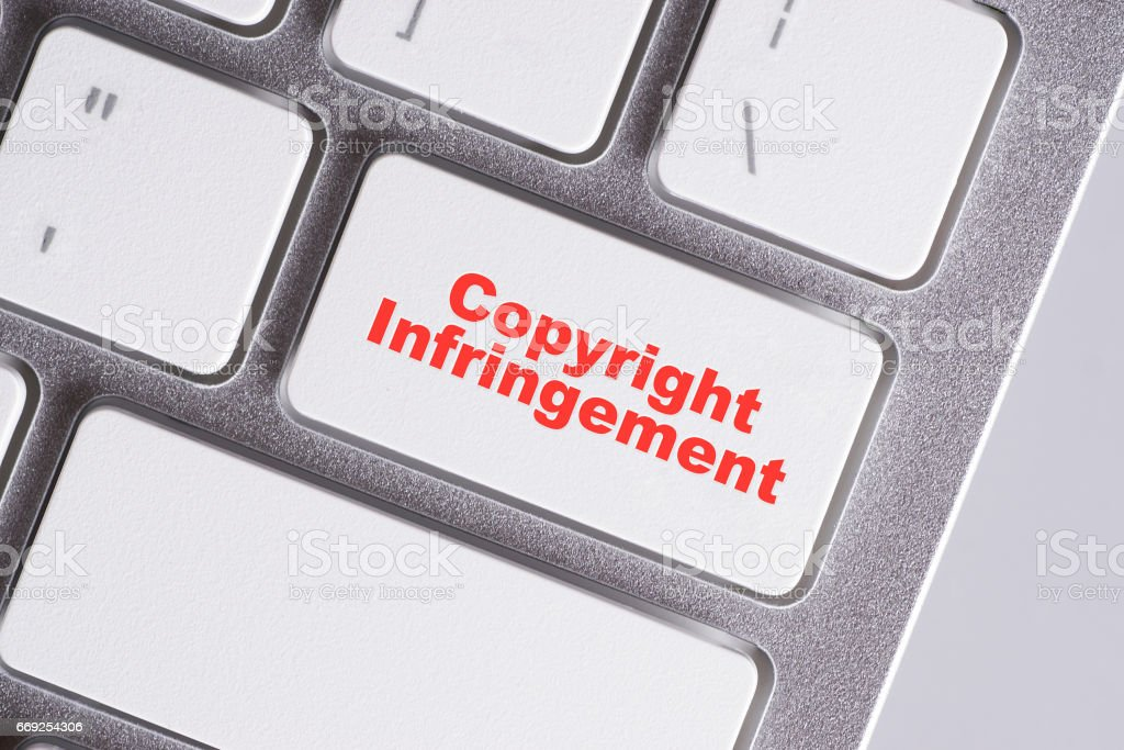 'Copyright infrigment' red words on white keyboard - online, education and business concept stock photo