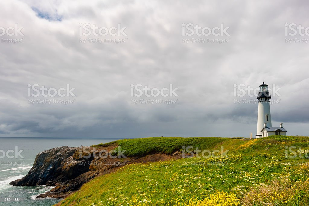copyspace Yaquina Head Lighthouse under cloudy skies stock photo