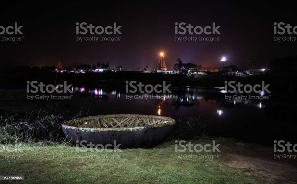 A coracle boat docked at the bank of Tungabhadra river, Virupaksha temple tower and temple in the backgroud. stock photo