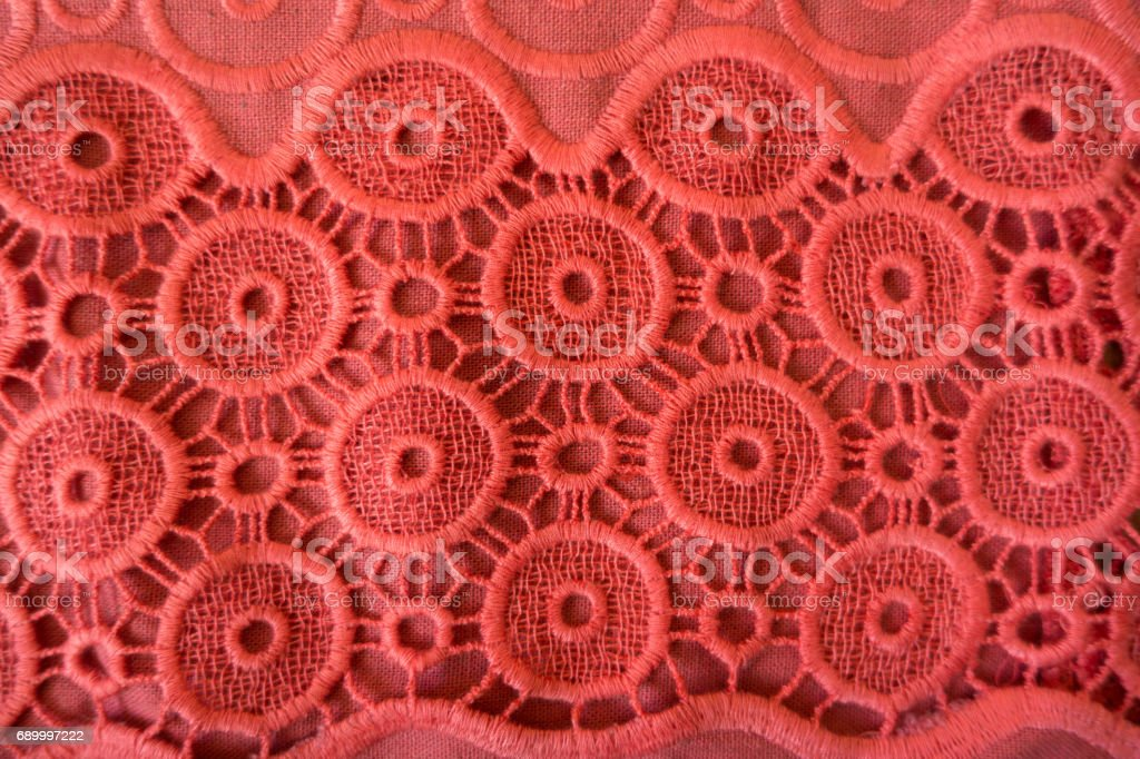 Coral red fabric with broderie anglaise from above stock photo