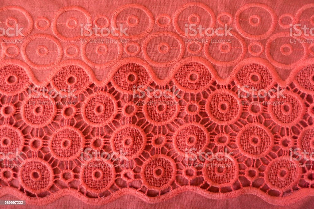 Coral red linen fabric with embroidered circles and crochet lace stock photo