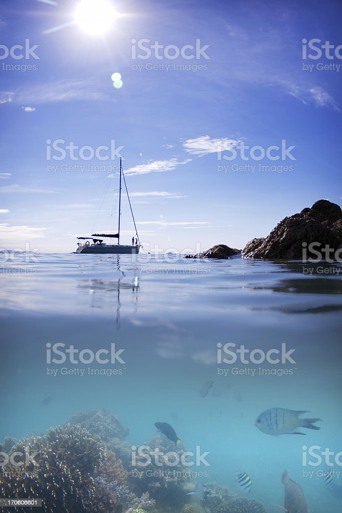 Coral Reef fish boat sun water and sky stock photo