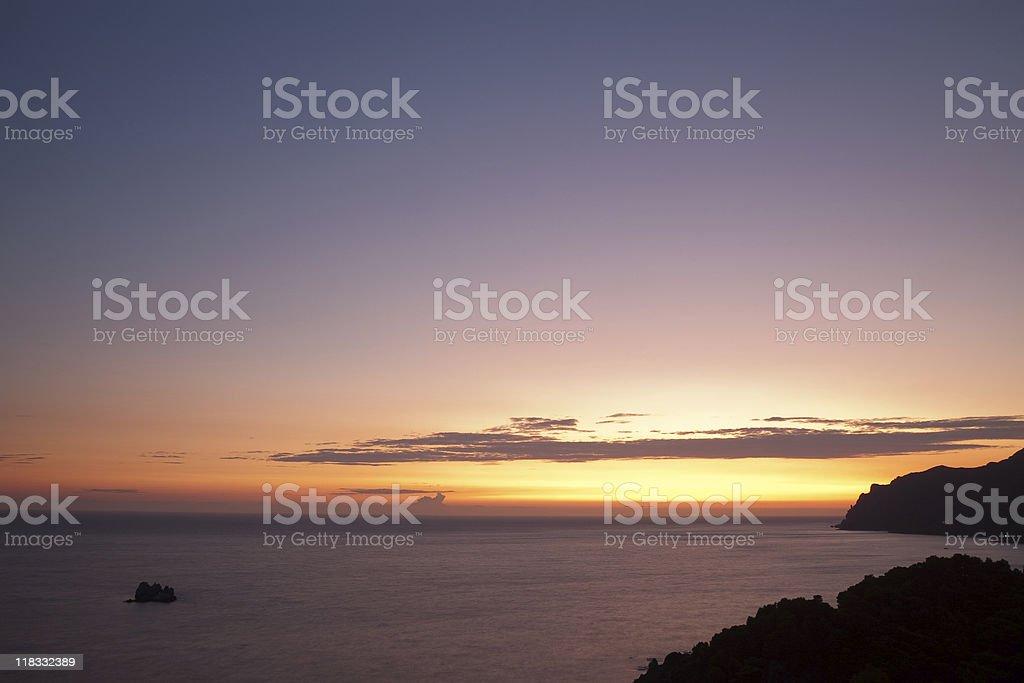 Corfu Sunset with rock stock photo
