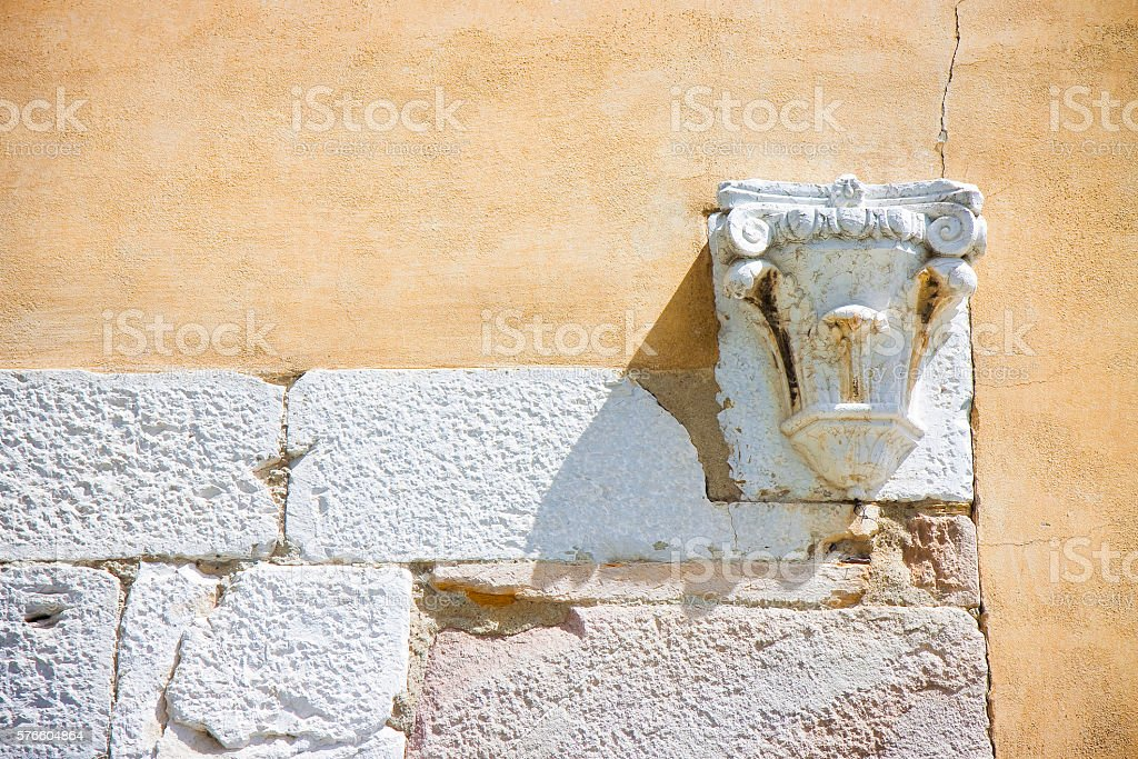 Corinthian capital in stone and plaster wall stock photo