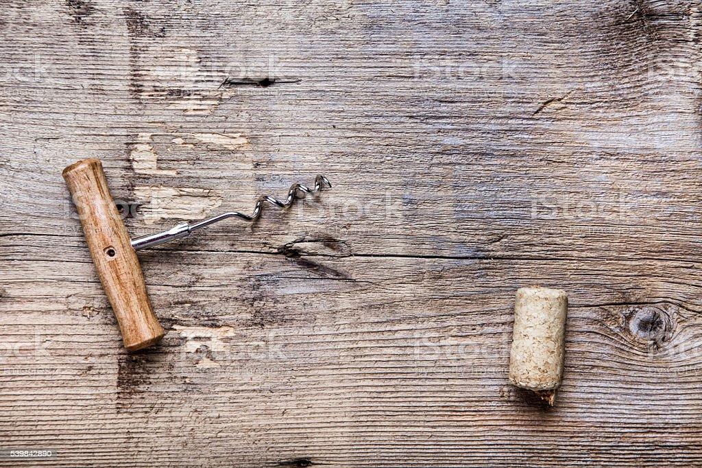 cork and corkscrew on wooden background stock photo