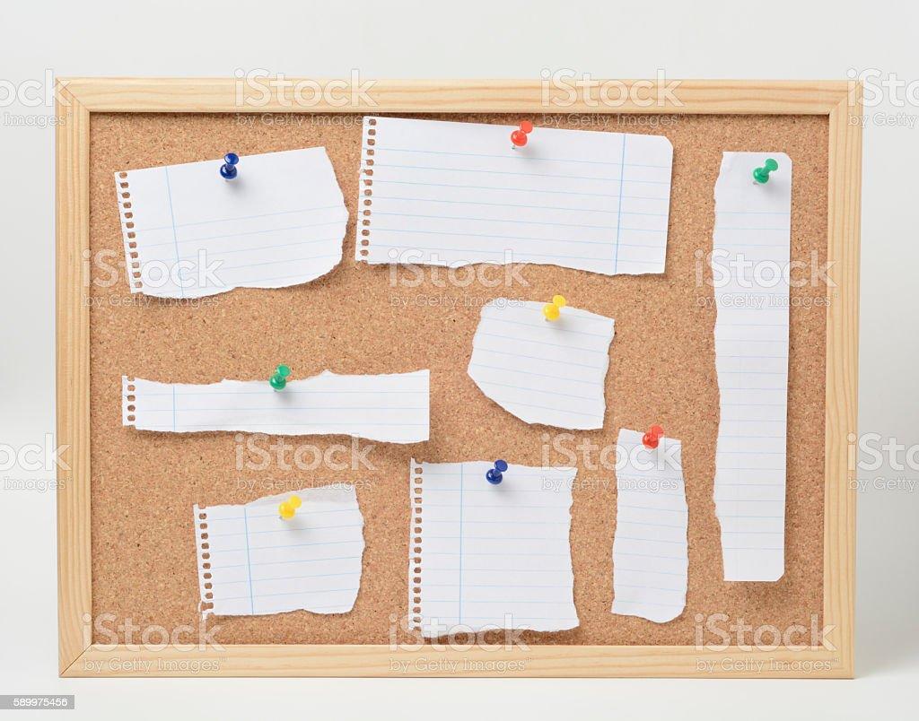 Cork board and paper scraps stock photo