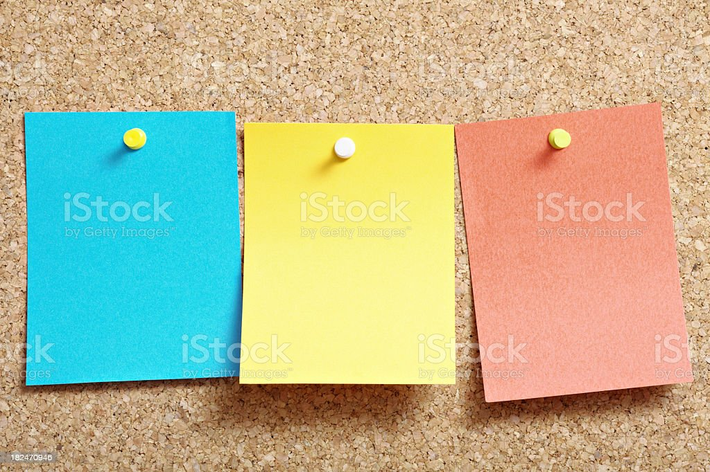 A cork board with three post it notes in blue yellow and red royalty-free stock photo