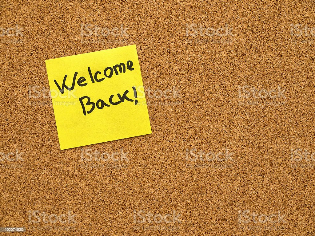 Cork board with welcome back post it note stock photo