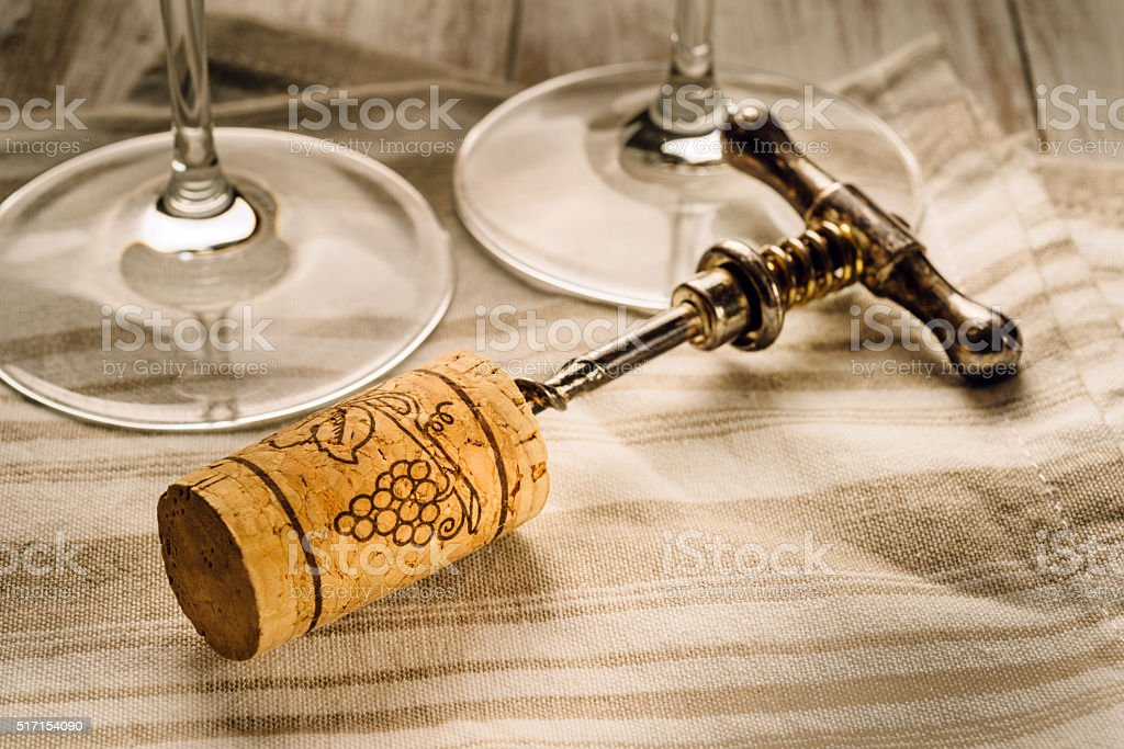 corkscrew, cork, wine glasses on the table stock photo