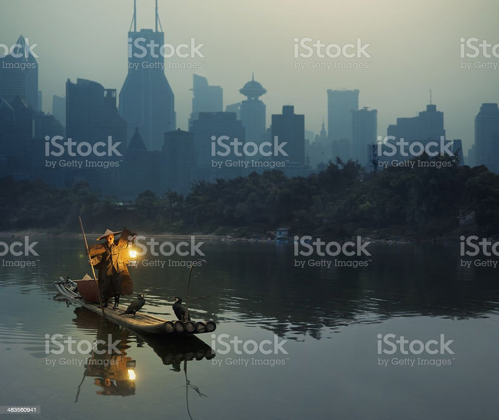 Cormorant fisherman in Shanghai against city background stock photo