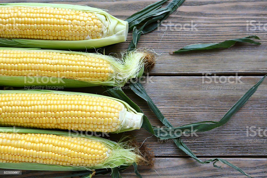 corn cob and green leaves on wooden background stock photo