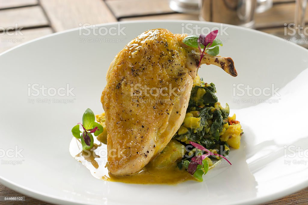 Corn fed chicken with sag aloo & curry veloute stock photo
