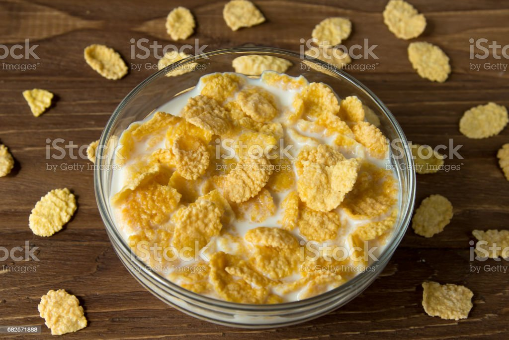 Corn flakes in a glass bowl with milk on a wooden surface stock photo