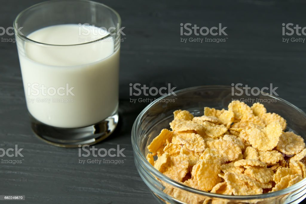 Corn flakes on glass bowl and glass of milk isolated on grey surface stock photo
