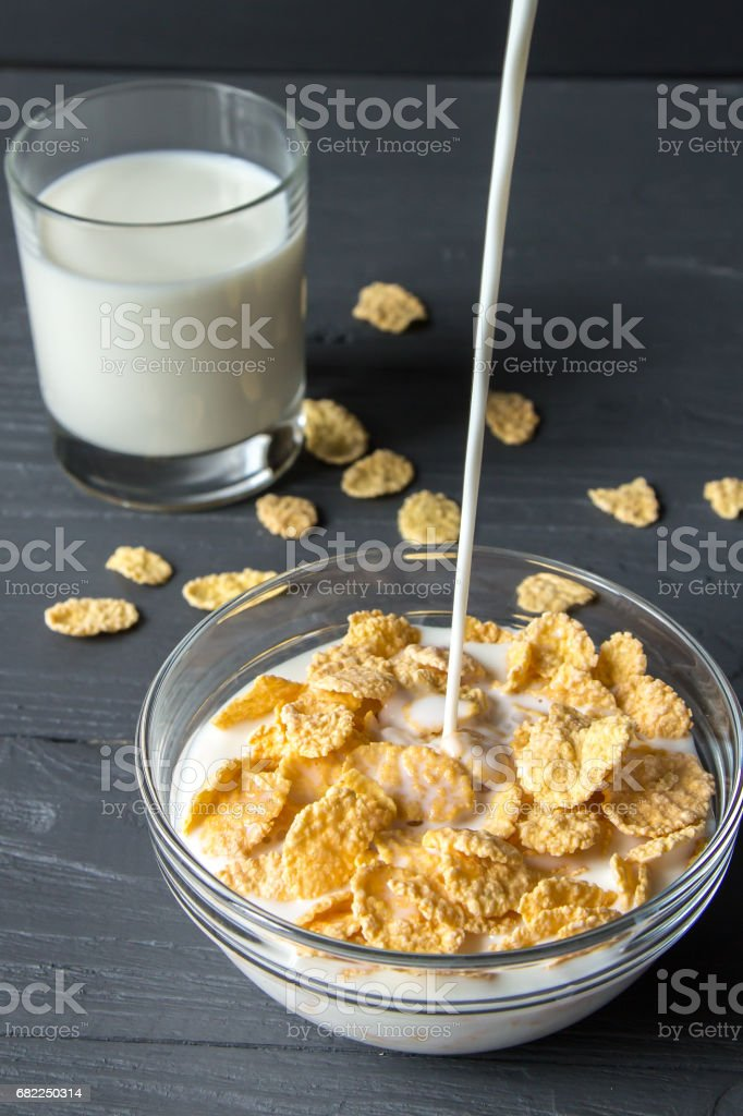 Corn flakes with flowing milk in a bowl stock photo